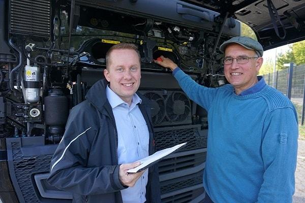 Dwusekundowi dealerzy samochodów ciężarowych dokonują oględzin ciężarówki, stojąc przed czarnym Volvo FH 460