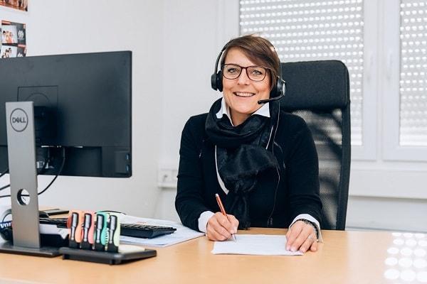 Kierownik odpowiedzialny za oferowanie używanych usług leasingu samochodów ciężarowych uśmiechając się przed jej biurkiem