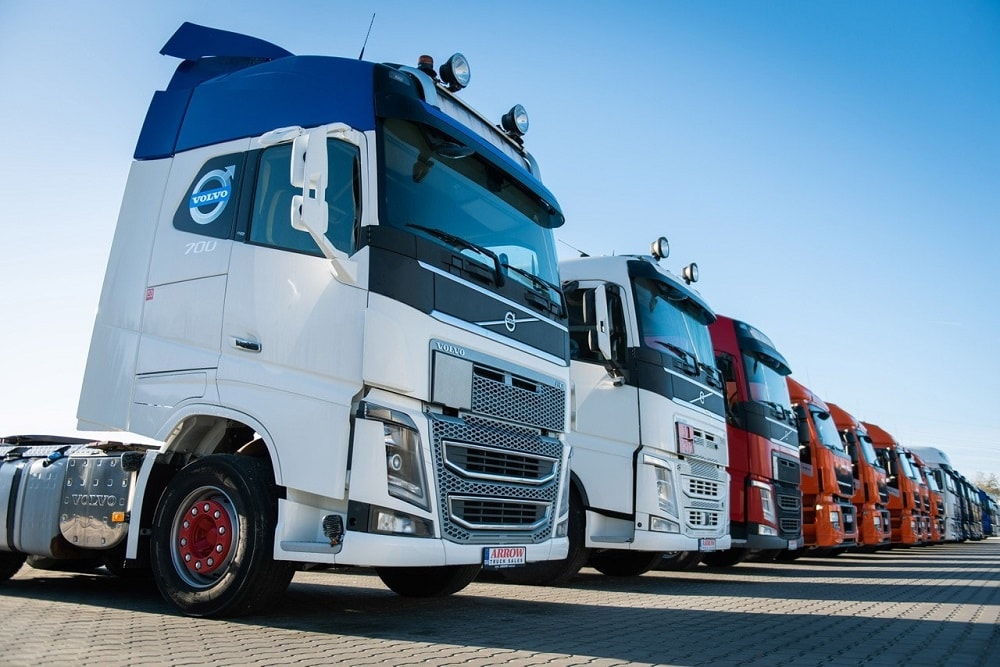 A line of used trucks for sale starting with a blue and white Volvo FH 700 among other trucks including IVECO and DAF